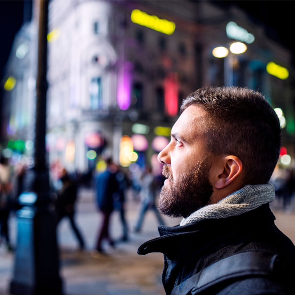 Man looking to the side in night time city